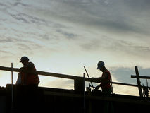 Silhouettes of workers. Workers at the construction site against the sun setting down stock photo