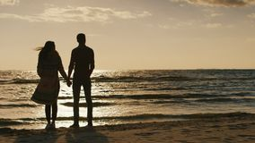 Couple in love looking at the sunset over the sea, holding hands. Cool day, the wind is blowing. Back view stock video