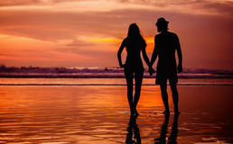 Silhouettes of young couple in love staing on the Stock Photos