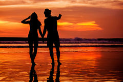 Silhouettes of young couple in love staing on the Stock Image