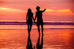 Silhouettes of young couple in love staing on the Royalty Free Stock Photos