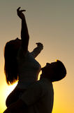 Silhouettes of young couple in love at sunset. Silhouettes of young couple in love on sunny summer day Stock Images