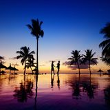 Silhouettes of young couple at scenic sunset stock image
