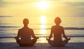 Silhouettes of a young couple sitting in the yoga Lotus position Royalty Free Stock Photography