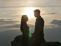 Silhouettes of young couple standing on a mountain and looking to each other on beautiful sunset background. Love of guy. And girl Royalty Free Stock Image