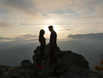 Silhouettes of young couple standing on a mountain and looking to each other on beautiful sunset background. Love of guy Stock Photo