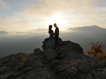 Silhouettes of young couple standing on a mountain and looking to each other on beautiful sunset background. Love of guy Royalty Free Stock Photography
