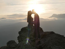 Silhouettes of young couple standing on a mountain and looking to each other on beautiful sunset background. Love of guy Royalty Free Stock Image