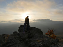 Silhouettes of young couple standing on a mountain and looking to each other on beautiful sunset background. Love of guy Royalty Free Stock Images