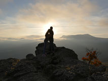 Silhouettes of young couple standing on a mountain and looking to each other on beautiful sunset background. Love of guy Stock Image