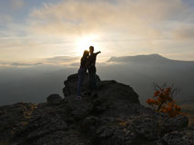 Silhouettes of young couple standing on a mountain and looking to each other on beautiful sunset background. Love of guy Stock Photography