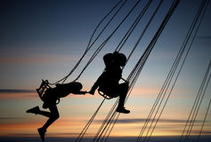 Silhouettes of young girls having fun on carousel Royalty Free Stock Images