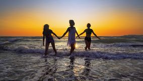 Silhouettes of young group of people jumping in ocean at sunset royalty free stock images