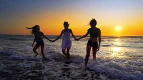Silhouettes of young group of people jumping in ocean at sunset stock photos