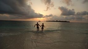 Silhouettes of young happy couple running to sunset in ocean holding hands in slow motion. Two lovers on honeymoon stock video footage