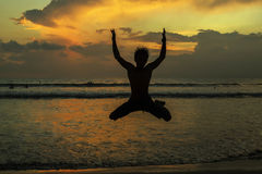 Silhouettes of young jumping boy at famous sunset beach in Kuta, Stock Photos