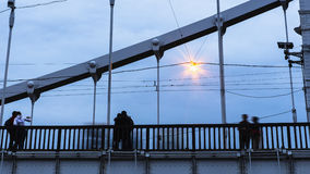 Silhouettes of young people on steel bridge in dusk. Silhouettes of young people on steel bridge Royalty Free Stock Images