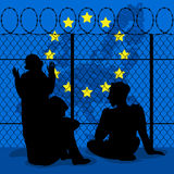 Silhouettes of young refugees, teenagers, children, sit behind t Royalty Free Stock Photos