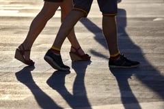 Silhouettez courir deux paires de jambes à la lumière du soleil de contre-jour Image stock