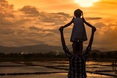 Silhouettez l'équitation asiatique de petite fille sur le father& x27 ; épaule de s Image stock