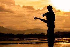 Silhouettez l'équitation asiatique de petite fille sur le father& x27 ; épaule de s Images stock
