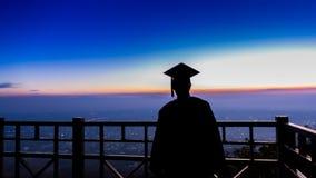 Silhouettez l'étudiant gradué contre le soleil se levant à la terrasse Photo stock