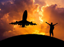 Silhouettez l'homme élevé vers le haut des accomplissements de bras réussis et célébrez pendant le vol d'avion dans le coucher du Photos stock