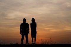 Silhouettez l'homme et la femme avec beau le ciel au coucher du soleil Backg Image libre de droits