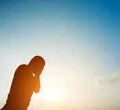 Silhouettez l'homme triste ou malheureux se tenant au-dessous du ciel Images stock
