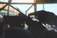 Silhouettez l'image d'une exploitation de main, dirigeant et à l'aide du comprimé image stock