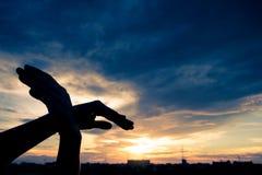 Silhouettez l'oiseau humain de forme de mains volant au-dessus du fond de ciel et de coucher du soleil Photos stock