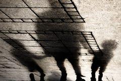 Silhouettez l'ombre d'un père tenant des mains avec deux petits garçons image libre de droits
