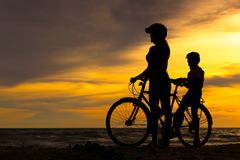 Silhouettez la belle famille de cycliste au coucher du soleil au-dessus de l'océan Maman et fille allant à vélo à la plage Image stock