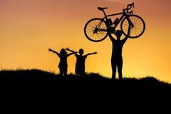 Silhouettez la bicyclette de levage d'homme au-dessus de sa tête avec la petite fille ayant l'amusement sur le coucher du soleil Photographie stock libre de droits