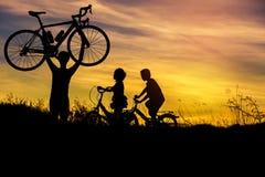 Silhouettez la bicyclette de levage de support d'homme au-dessus de sa tête avec le vélo d'équitation de petit garçon et de petit Photos libres de droits