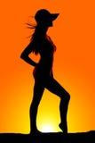 Silhouettez la femme dans un chapeau avec le soufflement de cheveux Image libre de droits