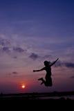 Silhouettez la femme heureuse sautant contre beau dans le coucher du soleil libre Photos stock