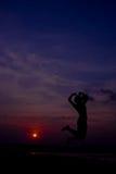 Silhouettez la femme heureuse sautant contre beau dans le coucher du soleil libre Image libre de droits