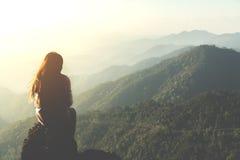 Silhouettez la femme s'asseyant sur la montagne dans le filt de matin et de vintage image libre de droits