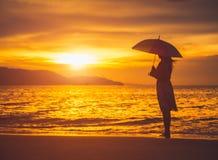 Silhouettez la femme seule et déprimée tenant un parapluie Image libre de droits