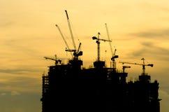 Silhouettez la grue de bâtiment et le bâtiment en construction contre la soirée Photo stock