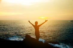 Silhouettez la jeune femme de bonheur sur la plage et la mer au coucher du soleil Image libre de droits