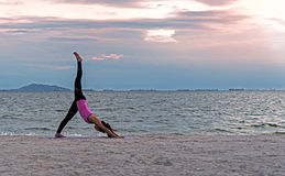 Silhouettez la jeune femme que l'exercice de mode de vie essentiel méditent et boule de pratique de yoga sur la plage au coucher  Images libres de droits