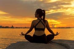 Silhouettez la jeune femme que l'exercice de mode de vie essentiel m?ditent et boule de pratique de yoga sur la plage au coucher  images libres de droits