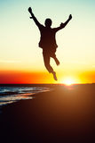 Silhouettez la jeune femme sautant avec des mains sur la plage au photos libres de droits