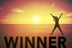 Silhouettez la jeune femme sautant et soulevant sa main au sujet de concept de gagnant sur le texte de gagnant au-dessus d'un bea Photographie stock libre de droits