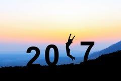 Silhouettez la jeune femme sautant par-dessus 2017 ans sur la colline au su Image libre de droits