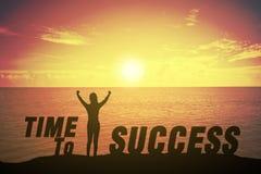 Silhouettez la jeune femme tenant et soulevant sa main au sujet de concept de gagnant à l'heure au texte de succès Image stock