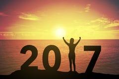 Silhouettez la jeune femme tenant et soulevant sa main au sujet de concept de gagnant dessus à 2017 au-dessus d'un beau coucher d Images libres de droits