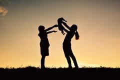 Silhouettez la mère et le garçon jouant avec le petit chien Photographie stock libre de droits